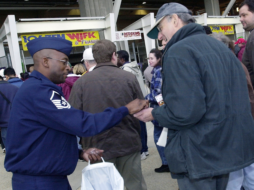 US Air Force (USAF) MASTER Sergeant (MSGT) Darren Rodgers, 317th Recruiting Squadron hands out USAF pins at the entrance to FedEx Field in Landover, Maryland (MD)