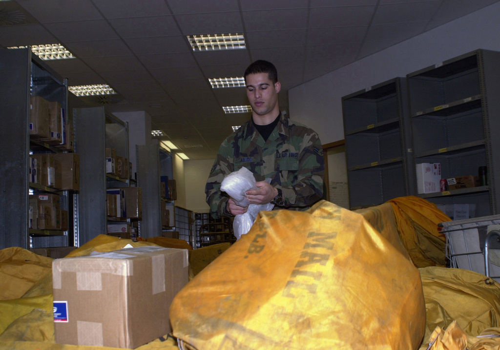 AIRMAN First Class (A1C) Ivan Abudo of the 786th Communications Postal Squadron's Northside Post Office, Ramstein Air Base, Germany, opens arriving mailbags