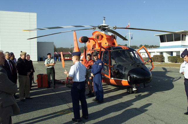 A Member of the US Coast Guard (USCG) Station at Savannah, Georgia (GA), brief members of the Georgia Military Affairs Coordinating Committee on search and rescue techniques at Hunter Army Airfield. An USCG HH-65A Dolphin short-range recovery helicopter is on display