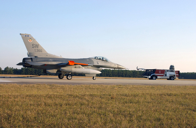 """A US Air Force (USAF) 55th Fighter Squadron F-16CJ, Fighting Falcon aircraft is brought to a stop on the runway during a barrier certification test at Shaw AFB, South Carolina (SC), during Operational Readiness Exercise Sea Lion 02-02. A K-15 Air Transportable Trans Continental Capable (ATTCC) """"Jaguar"""" Fire Tuck is parked in the background"""