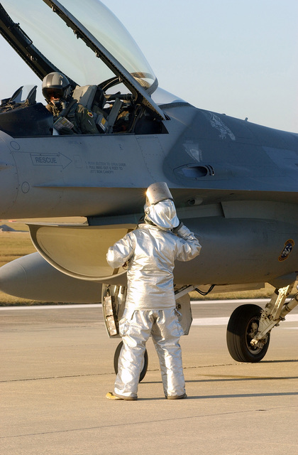 US Air Force (USAF) STAFF Sergeant (SSGT) Ernest Jillson, 20th Civil Engineering Squadron, Fire Department, talks with the pilot of a US Air Force (USAF) 55th Fighter Squadron F-16CJ, Fighting Falcon aircraft, following a barrier certification test at Shaw AFB, South Carolina (SC), during Operational Readiness Exercise Sea Lion 02-02