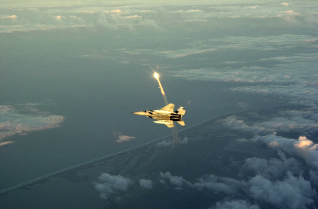 A Florida Air National Guard F-15C Eagle aircraft assigned to the 125th Fighter Wing (FW), flies a Air Patrol (CAP) mission as the Space Shuttle Endeavor launches from Cape Canaveral, Florida