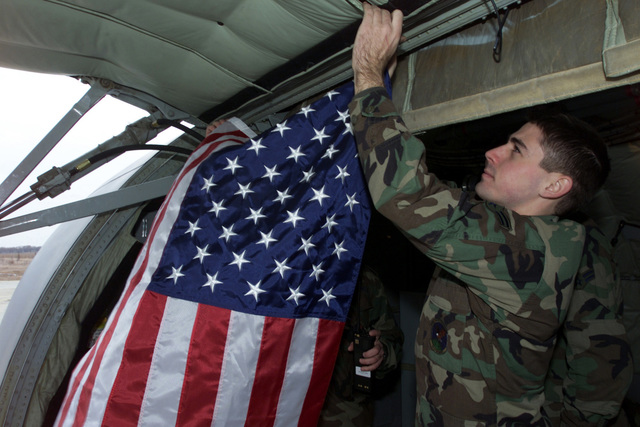 AIRMAN First Class (A1C) Nicholas Hoy, a Crew CHIEF from the 100th Aircraft Generation Squadron (AGS), Royal Air Force (RAF) Mildenhall, hangs a flag inside his KC 135R Stratotanker prior to an aerial refueling mission over the Black Sea, in support of Operation ENDURING FREEDOM