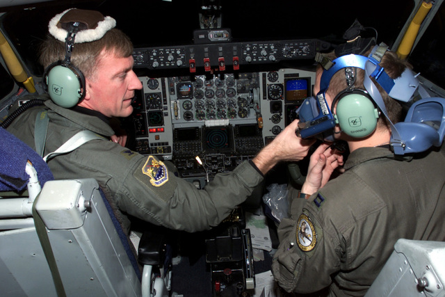 """Colonel (COL) Anthony Mauer, 100th Air Refueling Wing Operations Group Commander (ARWOGC) and Aircraft Commander (AC), assists Captain (CAPT) Devin Shanks, his co-pilot, with his emergency """"Quick Don"""" oxygen mask before flying a refueling mission, in support of Operation ENDURING FREEDOM"""