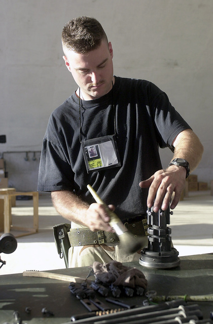 STAFF Sergeant (SSGT) Sean Taft, a weapons technician from the 16th Special Operations Wing (SOW), performs preventive maintenance on a GAU-2 mini gun, in support of Operation ENDURING FREEDOM