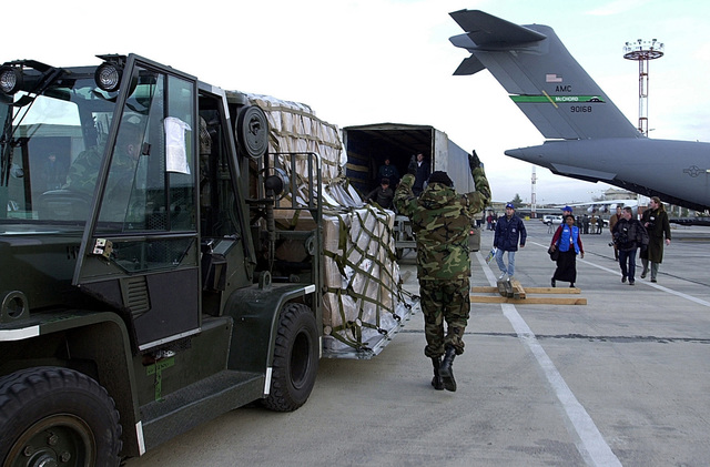 Members from the 97th Airlift Squadron, United States Air Force Reserves (USAFR), McChord Air Force Base (AFB), Washington and members of the 723rd Aerial Port Squadron (APS), Ramstein Air Base (AB), Germany, use a Hyser all glass enclosed cab materials handling forklift to unload pallets of humanitarian aid into the cargo bay of a C-17 Globemaster III cargo aircraft at Ashgabat, Turkmenistan