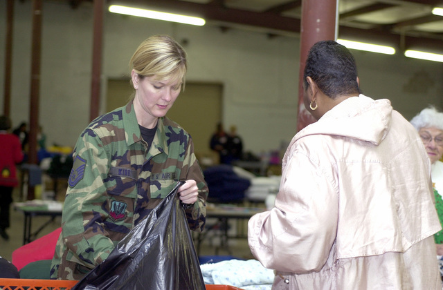 """US Air Force (USAF) MASTER Sergeant (MSGT) Brenda Kirby, Chaplain Assistant, 192nd Fighter Wing, Virginia Air National Guard, helps a mother shop for gifts during a donation drive called the """"Christmas Mother"""" program, at Byrd Field, Sandston, Virginia (VA)"""