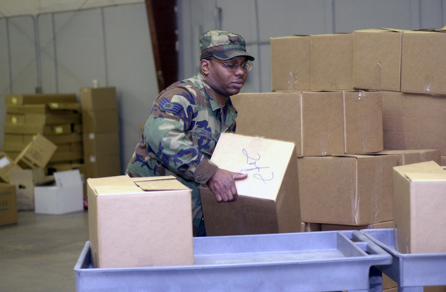 """US Air Force (USAF) STAFF Sergeant (SSGT) Alton Coston, Jet Engine Mechanic, 192nd Fighter Wing, Virginia Air National Guard, stacks boxes of food donated for under privileged children, during a donation drive called the """"Christmas Mother"""" program"""