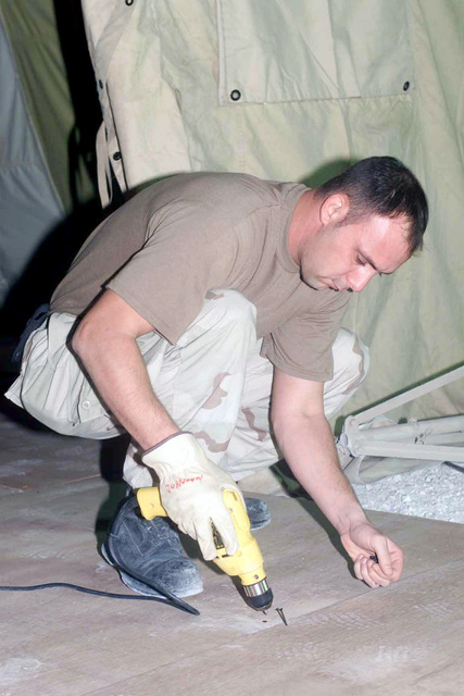 AIRMAN First Class (A1C) Kelley Johnson, 823rd Red Horse Squadron (RHS), from Hurlburt Field Air Force Base (AFB), Florida, prepares to screw together boards for a new tent floor at a forward location, in support of Operation ENDURING FREEDOM