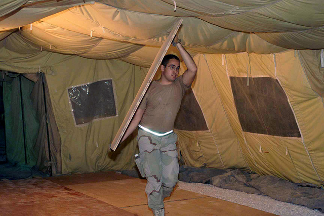 SENIOR AIRMAN (SRA) Steve Adamic, 823rd Red Horse Squadron (RHS), from Hurlburt Field Air Force Base (AFB), Florida, carries the next board used to make a tent floor at a forward location, in support of Operation ENDURING FREEDOM