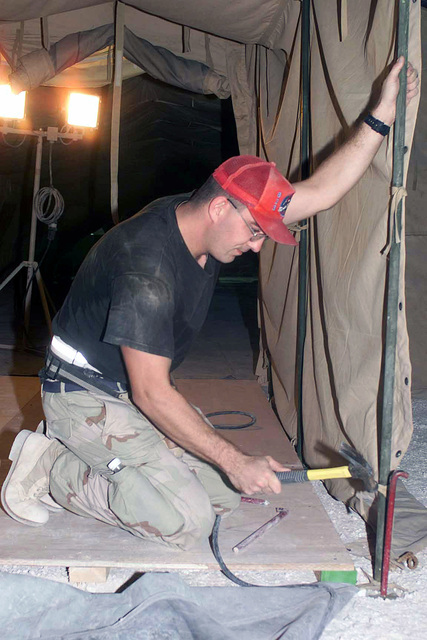 STAFF Sergeant (SSGT) Cory Kuntz, 823rd Red Horse Squadron (RHS), from Hurlburt Field Air Force Base (AFB), Florida, pounds in a tent stake, for the new location of the Communications Squadron, at a forward location, in support of Operation ENDURING FREEDOM
