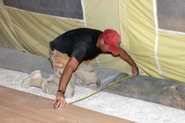 STAFF Sergeant (SSGT) Jody Lucas, 823rd Red Horse Squadron (RHS), from Hurlburt Field Air Force Base (AFB), Florida, measures the width for the next board in a tent floor at a base at a forward location, in support of Operation ENDURING FREEDOM