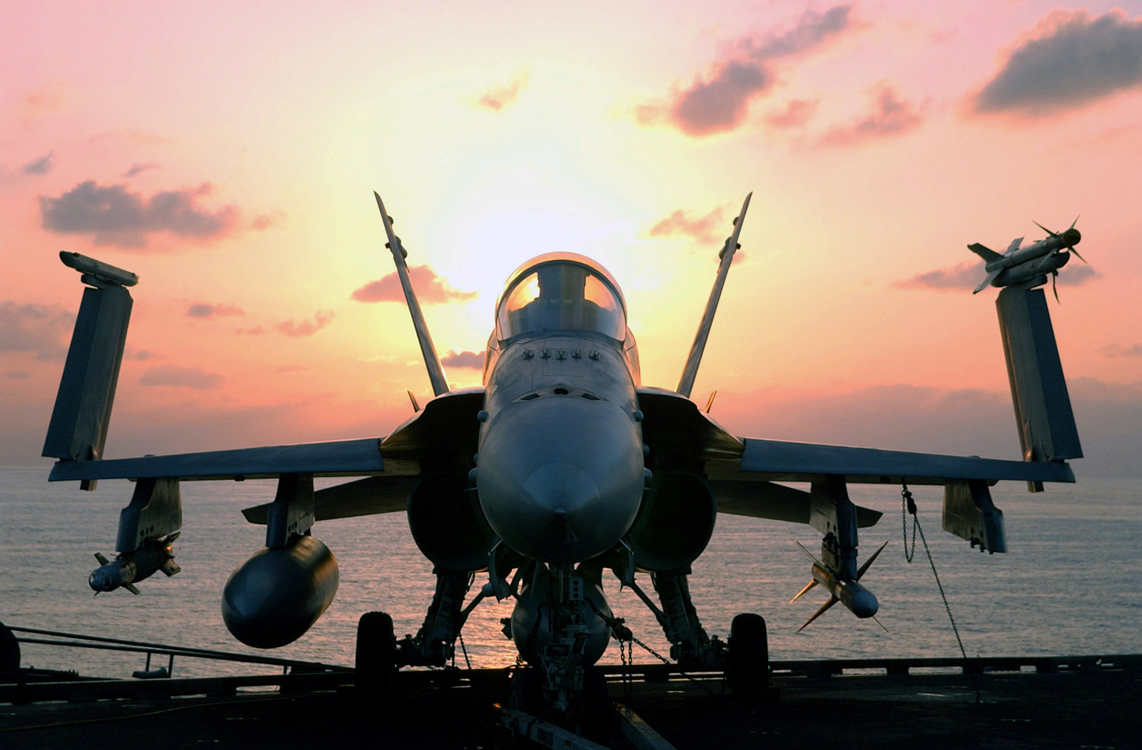 The sun rises on an F/A-18 Hornet on the USS John C. Stennis (CVN 74) after returning from a round of flight operations in support of Operation ENDURING FREEDOM. The Hornet is armed with an AIM-9 Sidewinder (right), AIM-7 Sparrow (right, lower) and a Laser Guided Mk-82 Bomb. The Hornet will soon be fully rearmed and along with the Stennis deployed Carrier Air Wing 9, continue in their full support of Operation ENDURING FREEDOM