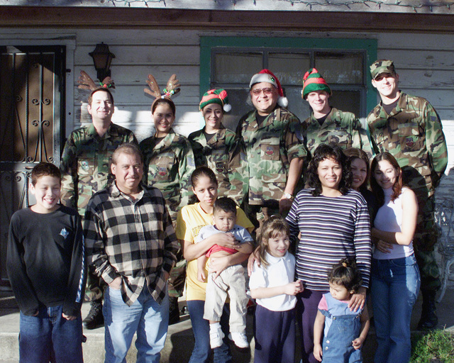 US Air Force (USAF) personnel assigned to the 149th Fighter Wing (FW), 182nd Operations Squadron, pose for a photograph with a local family from the Lackland Air Force Base, Texas (TX) community, during the 182nd Operations Groups adopt-a-family program