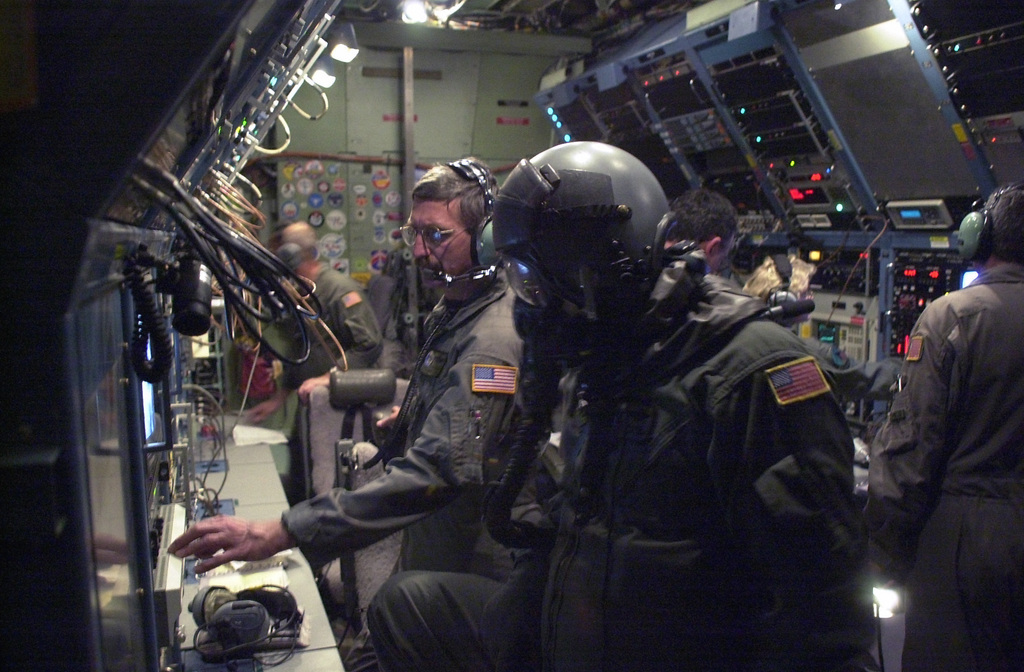 CHIEF MASTER Sergeant (CMSGT) James Bankes (foreground), USAF, electronics technician, 193rd Special Operations Wing (SOW), Pennsylvania Air National Guard (PANG), on the EC-130E Commando Solo, makes adjustments to the broadcast signal while wearing his helmet and mask in NBC configuration, accomplishing his periodic chemical warfare defense training. The 193rd SOW is currently flying Commando Solo missions in support of Operation ENDURING FREEDOM