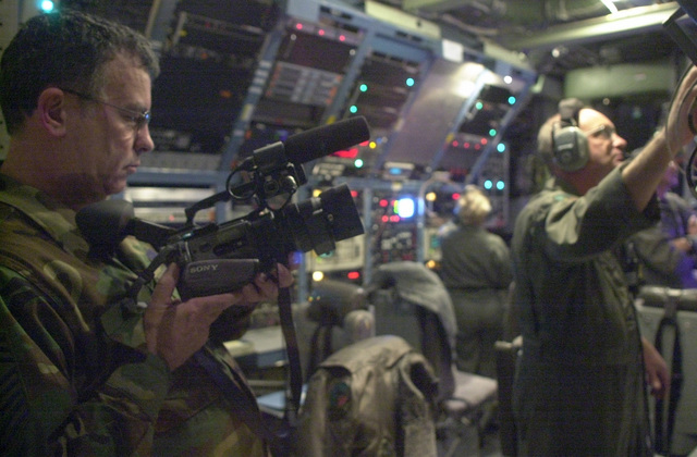 CHIEF MASTER Sergeant (CMSGT) Wayne Isett, (left), USAF, Multimedia Manager, 193rd Special Operations Wing (SOW), Pennsylvania Air National Guard (PANG), gets some video footage of MASTER Sergeant (MSGT) Barry Heine, USAF, electronics technician, 193rd SOW, PANG, during a training mission onboard the EC-130E Commando Solo. The 193rd SOW is currently flying Commando Solo missions in support of Operation ENDURING FREEDOM