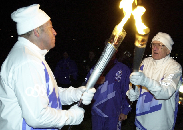 Korean War Veteran Mr. Glbert Lyons (left) passes the Olympic flame to World War Two (WWII) Veteran, US Air Force (USAF) Colonel (COL) (Retired) Frank E. Herrelko Sr., during his leg of the 2002 Olympic Torch Relay in Washington, D.C