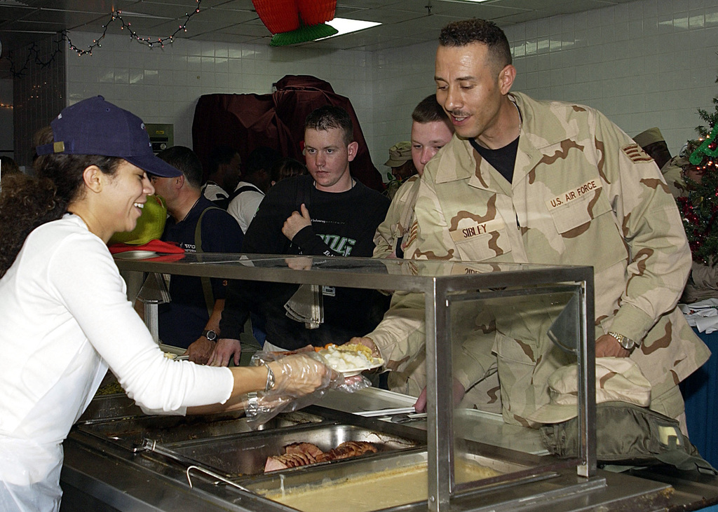 "Actress Sherri Saum, from the television daytime series ""One Life to Live"" serves Christmas dinner to US Air Force (USAF) personnel stationed at Prince Sultan AB, Saudi Arabia as part of the United Service Organizations (USO) Operation Starflight Freedom Tour"