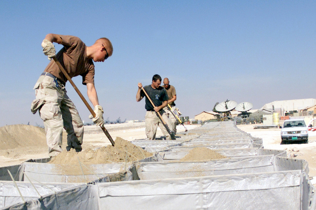 AIRMAN First Class (A1C) Derek Geske (left), SENIOR AIRMAN (SRA) Randy Fox (center) and A1C Boyd Clinton pack sand into expandable barriers at a forward location in support of Operation ENDURING FREEDOM
