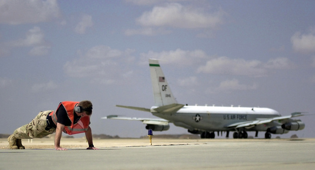 An Air Force RC-135V RIVET JOINT maintenance member from the 405th Air Expeditionary Wing (AEW) performs push-ups as his aircraft, taxiing away in the background, leaves for a mission during Operation ENDURING FREEDOM. The maintenance members of the RIVET JOINT complete a number of push-ups for every successful mission launch