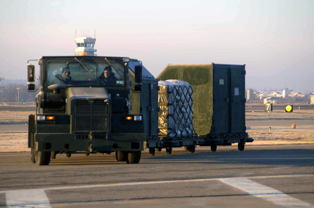 Using an aircraft tug, 188th Fighter Wing (FW), Arkansas Air National Guard (ARANG), Fort Smith, Cargo Deployment Function (CDF) load crew drive out to loading area in preparation for deployment to an undisclosed location