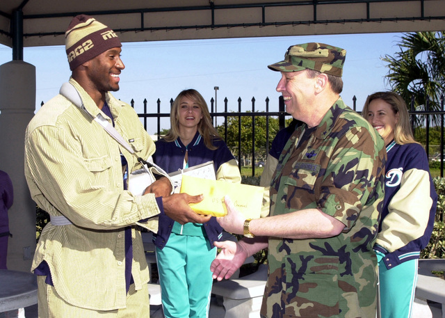 """Miami Dolphins Linebacker Derek Rogers presents 100 tickets to Brigadier General (BGEN) Charles E. Stenner, USAF, US Southern Command, for the Miami Dolphins playoff game Sunday with the Baltimore Ravens, the defending NFL champions. The tickets were made available under the NFL's """"Everyday Hero"""" program and will be handed out to the troops at SOUTHCOM. The Dolphins also brought four (two in the background) cheerleaders who signed autographs and handed out Dolphins calendars"""