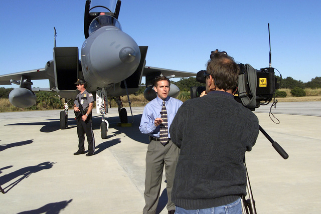 Phil Robertson, WFTV reporter CH 9, gives a live report from Canaveral Air Station, Orlando, Florida, while standing in front of an F-15C Eagle