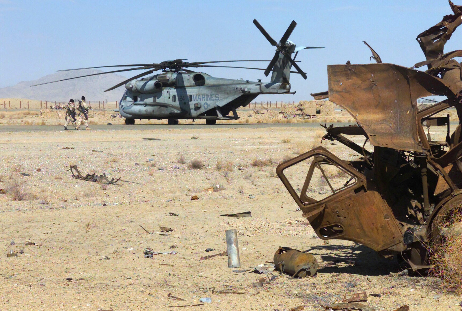 Two Marines walk along the runway toward a Marine CH-53 Sea Stallion helicopter with Marine Medium Helicopter -365 (HMM-365) (Reinforced) located at Khandahar International Airport, Khandahar, Afghanistan during OPERATION ENDURING FREEDOM. Just off the runway sits a large collection of destroyed Soviet equipment