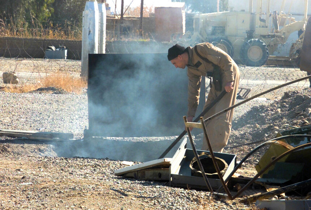 A Marine with Helicopter Marine Medium Squadron 365 (HMM-365) (Reinforced) tends a pit fire near the Air Command Element Headquarters at Kandahar International Airport, Kandahar, Afghanistan, during OPERATION ENDURING FREEDOM