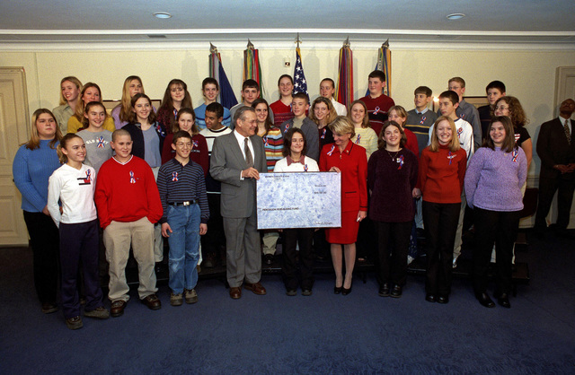 The Honorable Donald H. Rumsfeld, U.S. Secretary of Defense, accepts a check for rebuilding the Pentagon, from the 8th grade class of Moorefield Middle School, Moorefield, W. Va., during a ceremony, also attended by Rep. Shelley Moore Capito (to the right of the check), R-W. Va., at the Pentagon, Washington D.C., on Jan.15, 2002.  Lasidi Helmick (behind check) formulated the idea for the contributions. (DoD photo by Robert D. Ward)  (Released)
