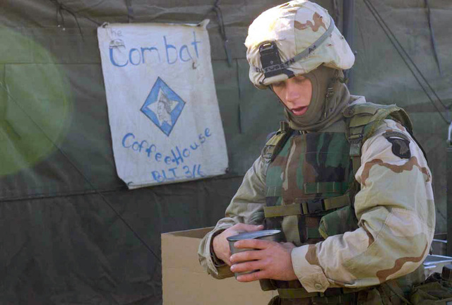 A Army soldier with the 101st Airborne Division, enjoys a warm cup of coffee, couresy of Marine cooks with the 26th Marine Expeditionary Unit (Special Operations Capable) (MEU(SOC)), at International Airport, Kandahar, Afghanistan, during OPERATION ENDURING FREEDOM