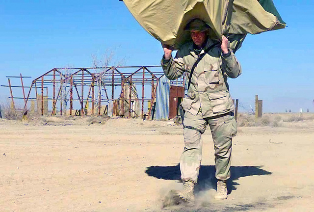 A Marine with 2d Combat Engineer Battalion, Battalion Landing Team 3/6, 26th Marine Expeditionary Unit (Special Operations Capable) relocates his two-man desert colored dome tent at Kandahar International Airport, Kandahar, Afghanistan, during OPERATION ENDURING FREEDOM