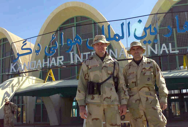 Lieutenant Colonel Jonathan D. Covington, USMC (left), and Major Mark Schrecker, USMC (lright), pilots with the Marine Central Command Combat Assessment Team, stand in front of the Kandahar International Airport, Kandahar, Afghanistan, during OPERATION ENDURING FREEDOM