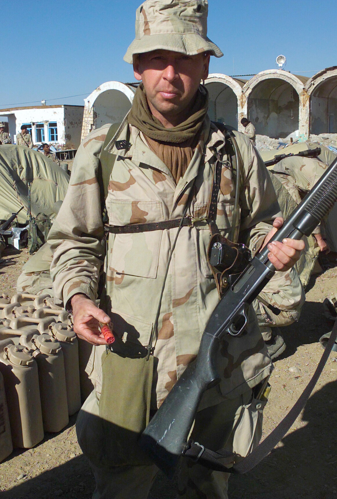First Sergeant Rickie McCall, USMC, First Sergeant of Kilo Company, Battalion Landing Team 3/6, 26th Marine Expeditionary Unit (Special Operations Capable) (MEU(SOC)) poses with his Remington 879 shotgun and a holdstered M-9 pistol at Kandahar International Airport, Kandahar, Afghanistan, during OPERATION ENDURING FREEDOM