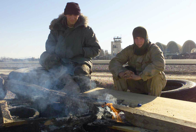 Marines Corporal William Robinson and Lance Corporal Marcus Rouston (left to right), members of Marine Wing Support Squadron 273, 26th Marine Expeditionary Unit (Special Operations Capable) (MEU(SOC)) warm themselves around a wood fire near the Forward Aerial Refueling Point (FARP) at the Kandahar International Airport, Kandahar, Afghanistan, during OPERATION ENDURING FREEDOM