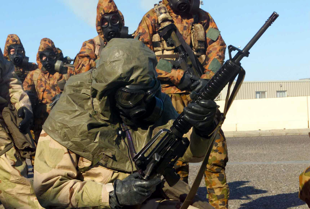 A Marine with Combined Joint Task Force (CJTF) dressed in his Joint Service Lightweight Integrated Suit Technology (JSLIST), wearing an M40 Chemical-Biological Field Mask with a C2A1 filter canister, assembles a 5.56 mm Colt M16A2 Assault Rifle during training with service members from Australia, wearing their MKIV No1 NBC (Nuclear Biological Chemical) Suits with Avon FM12 Mask. At Camp Doha, Kuwait during OPERATION ENDURING FREEDOM