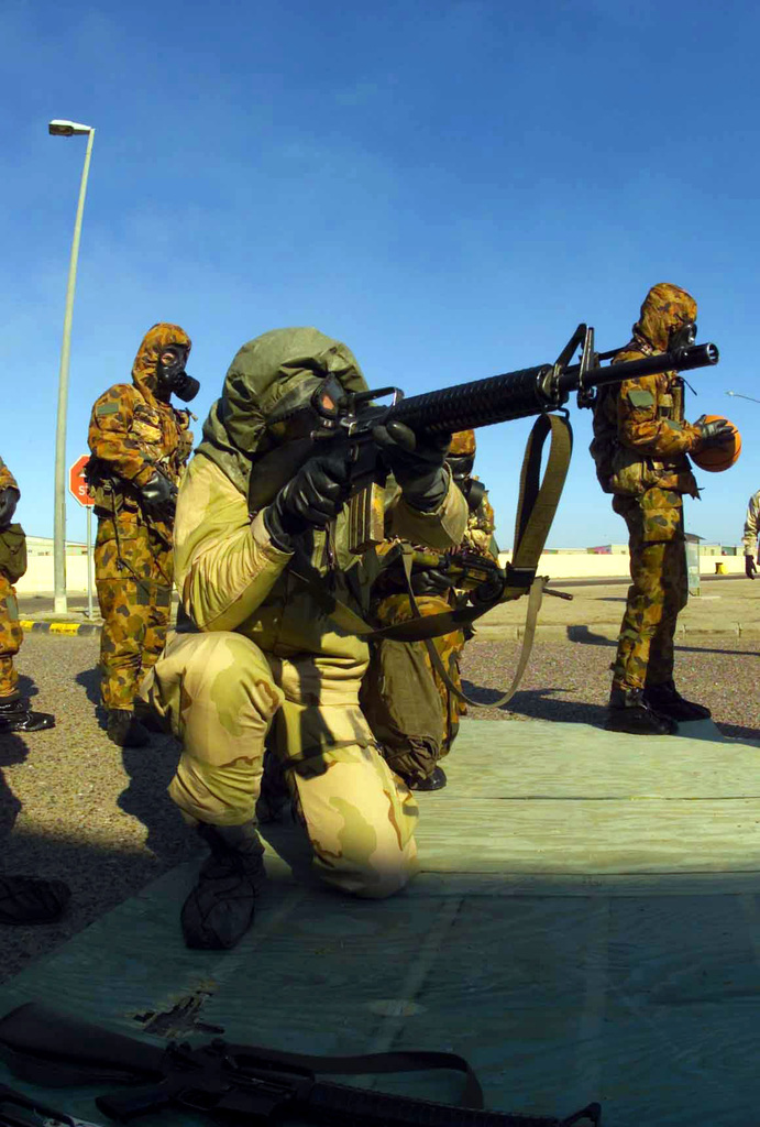 A Marine with Combined Joint Task Force (CJTF) in his Joint Service Lightweight Integrated Suit Technology (JSLIST), wearing an M40 Chemical-Biological Field Mask with a C2A1 filter canister aims at the designated target after assembling his M16A2 Assault Rifle during training at Camp Doha, Kuwait during OPERATION ENDURING FREEDOM. In the background are two Australian competitors in their MKIV No1 NBC (Nuclear Biological Chemical) Suits with Avon FM12 Mask