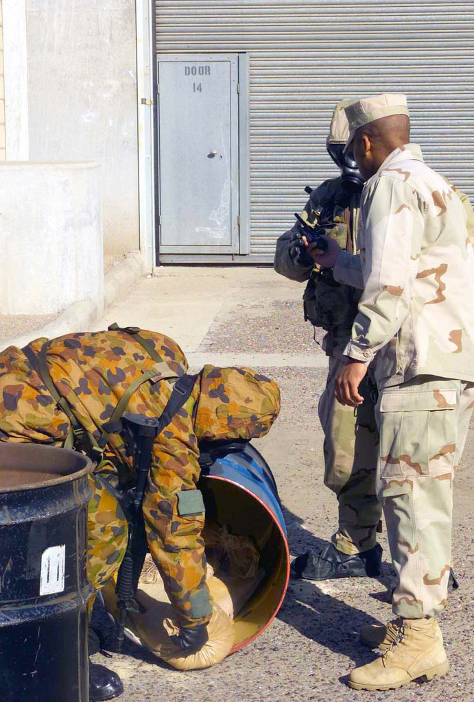 Working in full NBC (Nuclear Biological Chemical) gear, a Marine and Australian as a team rolled a barrel full of sandbags, now prepare to remove the sandbags. Evaluator STAFF Sergeant Calvin R. Young (right), USMC, Radio Operator from 9th Communication Battalion attached with the Combined Joint Task Force (CJTF) monitors the activity. The Australian (left) is wearing his MKIV No1 Suit with Avon FM12 Mask. He also has his 5.56mm Colt M4 Carbine slung across his back. The Marine (rear) is dressed in his Joint Service Lightweight Integrated Suit Technology (JSLIST), wearing an M40 Chemical-Biological Field Mask with a C2A1 filter canister. The Marines and Australians are in NBC training at ...