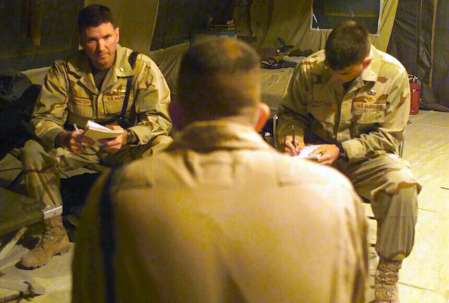 """Lieutenant Colonel Jonathan """"JD"""" Covington, USMC, (left) and Major Mark """"PigPen"""" Schrecker, USMC, both members of the Marine Central Command Combat Assessment Team, interview Major Dwight Neeley, USMC, Detachment Commander, Marine Aerial Refueler Transport Squadron VMGR 352, at a forward operating base in the Operation ENDURING FREEDOM area of operations"""