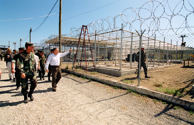 The Honorable Donald H. Rumsfeld (foreground, right), U.S. Secretary of Defense (SECDEF), checks on the condition of the 158 Taliban and Al-Qaeda detainees at Camp X-Ray, Guantanamo Bay, Cuba, Jan. 27, 2002.  The SECDEF is in the area to check on the detainees and to visit the troops. (DoD photo by Helene C. Stikkel) (Released)