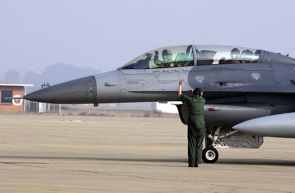 """US Air Force (USAF) Lieutenant Colonel (LTC) Pat Miller (pilot) and Crew CHIEF, USAF SENIOR AIRMAN (SRA), Hudson, exchange the traditional """"Buzzard Claw"""" sign prior to an incentive ride for (Back Seat) crew chief USAF AIRMAN First Class (A1C) Pedro Campos, as the two taxi out aboard a USAF F-16D Fighting Falcon, on the flight line at Zaragoza AB, Spain"""