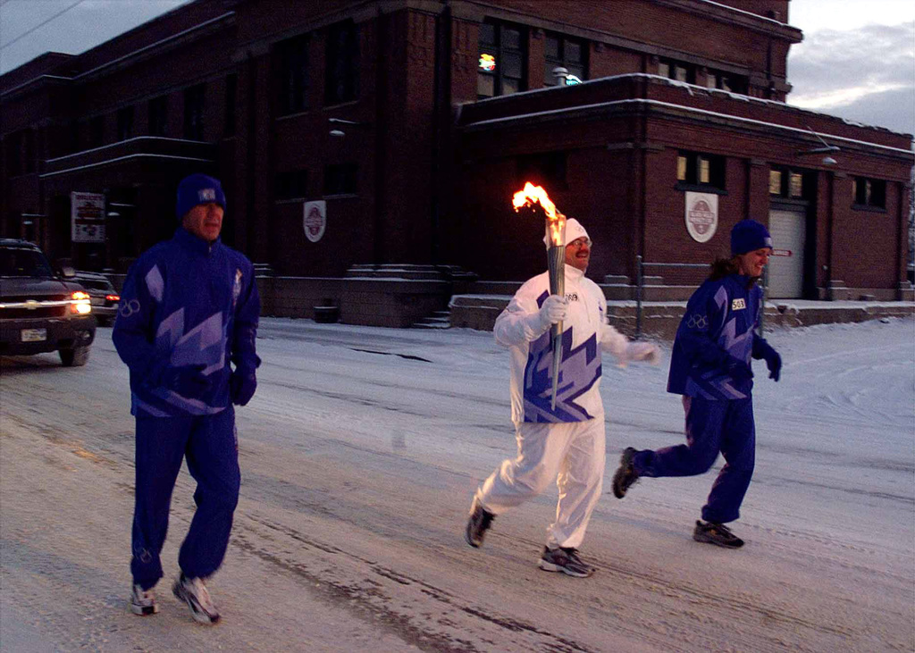 US Air Force (USAF) Technical Sergeant (TSGT) Mark Carnes (center), 28th Services Squadron, 28th Bomb Wing, is escorted by two other runners as he carries the Olympic flame down Broadway Street in Sheridan, Wyoming. SSGT Carnes is one of 11,500 people selected to carry the torch during the 2002 Winter Olympic Torch Relay