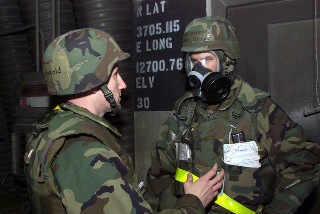Captain (CAPT) Steven Harrold, USAF, 51st Fighter Wing (FW), Exercise Evaluation Team (EET), provides feedback to Major (MAJ) Bryan Manes, in Mission-Oriented Protective Posture response level 4 (MOPP-4) gear, 36th Fighter Squadron (FS), during Exercise BEVERLY BULLDOG at Osan Air Base, Republic of Korea