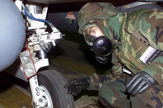 SENIOR AIRMAN (SRA) Jacob Horseman, USAF, Crewchief, 36th Fighter Squadron (FS), in Mission-Oriented Protective Posture response level 4 (MOPP-4) gear, inspects the landing gear of an F-16 Fighting Falcon during BEVERLY BULLDOG exercise at Osan Air Base, Republic of Korea