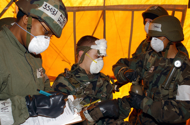 AIRMAN First Class (A1C) Natasha Huff (left), USAF, writes down patient information on a chart while others comfort A1C Jarrod Woods, (center), USAF, the simulated patient, as he is in-processed into the 20th Emergency Medical Evacuation Dental Squadron (EMEDS) field hospital.  All are participating in the Operational Readiness Inspection (ORI) CORONET WHITE 02-07 at Shaw AFB, South Carolina