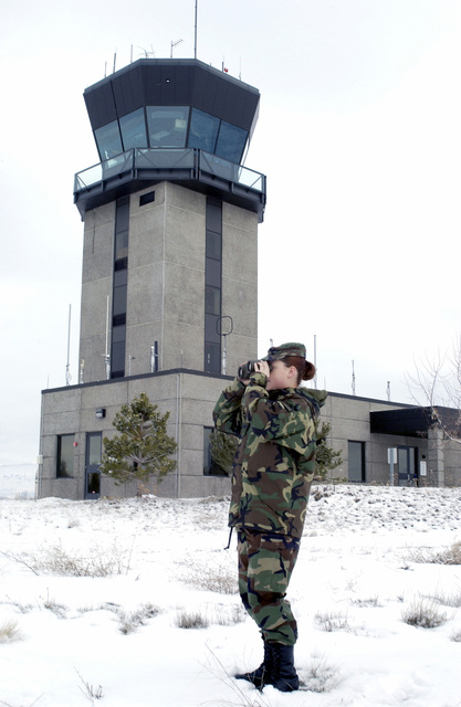 From the base of the control tower, SENIOR AIRMAN (SRA) Crystal Thorton, USAF, 270th Air Traffic Control Squadron (ATCS), searches the horizon for a snow plow clearing the runways after a storm covered Kingsley Field with a blanket of snow