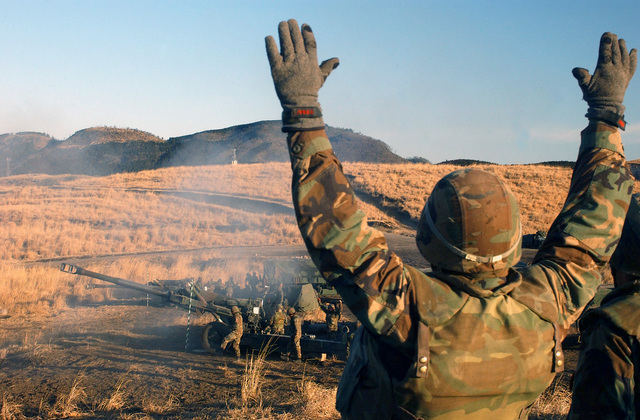 US Marine Corps (USMC) Corporal (CPL) Miremotes, with the 3rd Battalion, 12th Marines, Tango Battery, cheers as the first shot of the day is fired from his crews M198 Towed Howitzer, during a live fire artillery mission, on the Hijudai Training Grounds, Oita, Japan