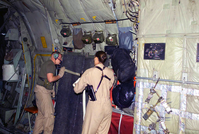 Marine Aerial Refueler Transport Squadron-352 (VMGR-352) Loadmasters, Sergeant (SGT) Jessica Lujick, USMC, (right) and Corporal Matthew Rider, USMC, (left) secure the ground ramp extensions to the inside of the KC-130/R before take-off. They completed the delivery of 26th Marine Expeditionary Unit (Special Operations Capable) (MEU (SOC)) Marines and supplies to the Kandahar Airport in Afghanistan during Operation ENDURING FREEDOM. SGT Lujick is has her crew weapon strapped to her, a 9 mm Beretta M9 Semiautomatic Pistol