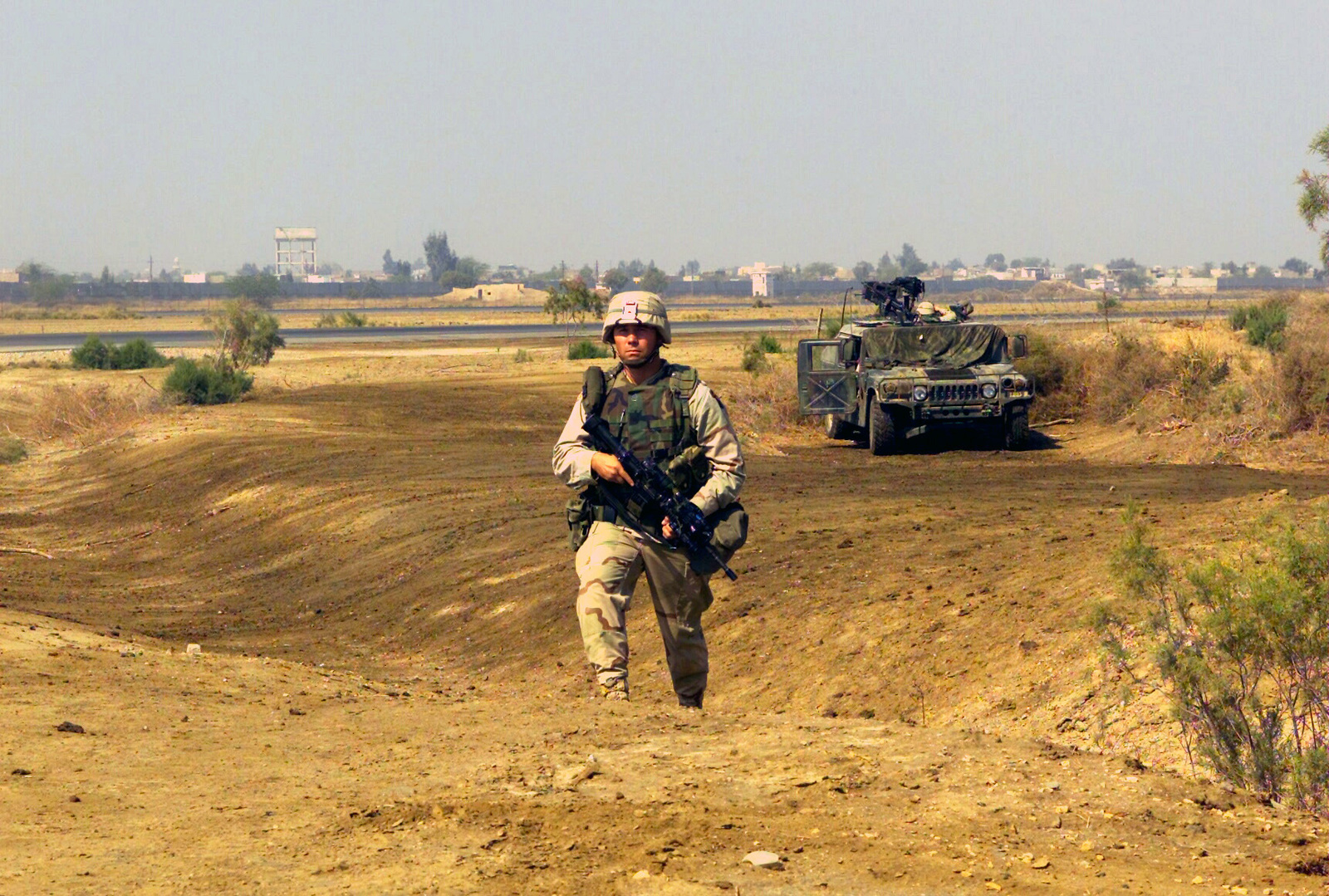 STAFF Sergeant Thomas E. Dougherty, Squad Leader, 1ST Platoon, 1ST Battalion, 187th Infantry Regiment makes his rounds during a spot check on the security post at a forward operating base in the Operation ENDURING FREEDOM area. In the background an armed M1043 High-Mobility Multipurpose Wheeled Vehicle (HMMWV) and crew standby