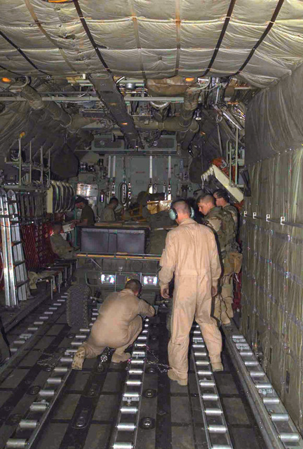 """While the Army crew stands by, Loadmasters from Marine Aerial Refueler Transport Squadron-252 (VMGR-252), secure an Army John Deere 6X4 """"Gator"""" All Terrain Vehicle (ATV) to the deck of their KC-130/R before a flight into Kandahar, Afghanistan in support of the Army during Operation ENDURING FREEDOM"""